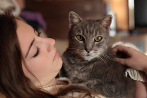 owner looking lovingly at cat wondering if her cat knows how much they are loved
